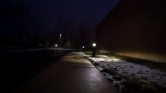 Walking down poorly-lit sidewalk in the dark Stock Footage