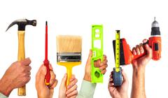 Hands of handyman with tools. - stock photo
