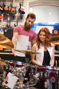 Man and woman with drum kit at music store Kuvituskuvat