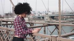 Stock Video Footage of Afro American Female standing on Brooklyn bridge on smart phone