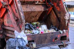Garbage truck keeping garbage on urban street. Stock Photos