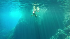 Couple swimming and diving in cave, Bisevo island, Croatia Stock Footage