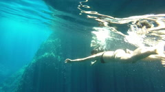Couple swimming and diving in cave, Bisevo island, Croatia - stock footage