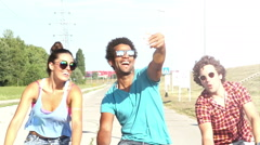 Three young adults having fun cycling and taking selfies, graded - stock footage