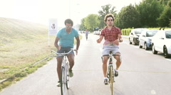 Three young adults having fun cycling, graded - stock footage