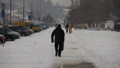 Rendom, unrecognizable pedestrian walking away along snowy covered path Stock Footage