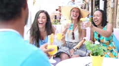 Three female friends drinking cocktails on terrace cafe in summer Stock Footage
