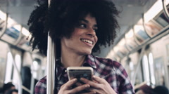 Afro American Female on subway with smart phone Stock Footage