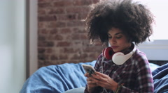 Afro American Female with smart phone, wearing headphones - stock footage