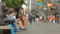 Young men sitting and relaxing on Kärntner Strasse, Vienna Stock Footage
