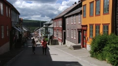 Tourists walk by street of Roros in Roros, Norway. Stock Footage