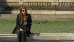 Young woman sitting in a square and listening music, Vienna Stock Footage