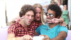 Three young adults having fun taking spontaneous selfies - stock footage