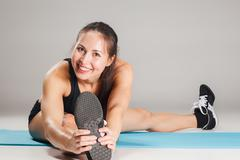 Muscular young woman athlete stretching on gray - stock photo