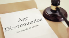 Age Discrimination verdict folder with gavel placed on desk of judge in court Stock Footage