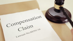 Compensation claim lawsuit documents with gavel placed on desk of judge Stock Footage