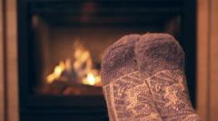 Feet in woollen socks by the fireplace - stock footage