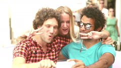 Two men and woman having fun taking spontaneous selfies - stock footage