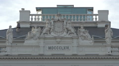 Building from 1864 with statues and coat of arms sculpture in Vienna Stock Footage