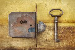 Ancient door lock with key on a metal background - stock photo