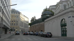 Driving cars and motorcycle along a white imposing building in Vienna Stock Footage