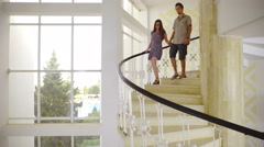Couple walk down spiral stairs in big building  Stock Footage
