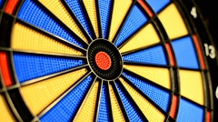 Missing the target bull's eye at dart game closeup Stock Footage