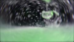 Green liquid flowing in water, bubbles floating - black background  Stock Footage