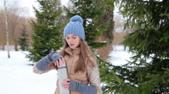 Girl drink hot tea in a thermos in snowy forest Stock Footage