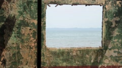 POV of Ocean Through Window Openings in Abandoned Prison Stock Footage