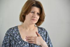 Woman with pain in  chest, angina - stock photo