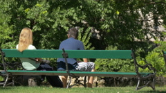 Couple sitting on a bench in Burggarten, Vienna Stock Footage