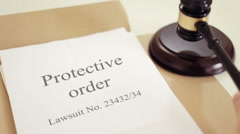 Protective order with gavel placed on desk of judge in court - stock footage