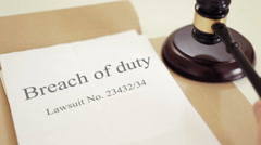 Breach of duty lawsuit verdict with gavel placed on desk of judge in court - stock footage