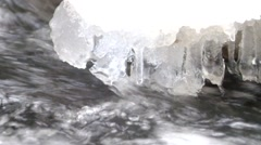 Small icicles glitter above milky blurred water of noisy stream. - stock footage
