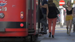 People boarding a red tram in Vienna Stock Footage