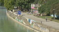 Riding a bike on the Danube Canal waterfront in Vienna Stock Footage