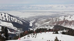 Top view on ski resort of Karakol, paraglider, and city in valley Stock Footage