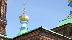 Roof of wooden Orthodox Holy Trinity Cathedral in Karakol, black bird drinking Stock Footage