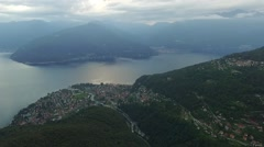 Aerial shot of lake maggiore with village and mountains at dawn Stock Footage