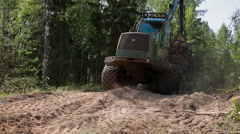 Feller Buncher  drives from the forest Stock Footage