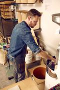 Man working with a modern coffee bean roasting machine Stock Photos