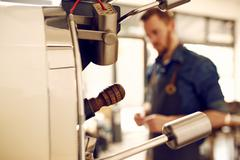 Coffee bean roasting machine with man in the background Stock Photos