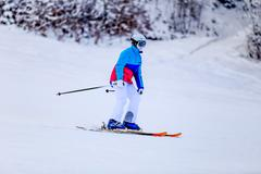 Woman in white skiing suit on mountain slope Stock Photos
