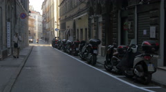 Man walking, cars and scooters driving near parked scooters in Trieste Stock Footage
