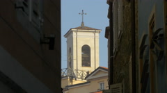 View of a church tower seen between buildings in sunlight in Trieste - stock footage