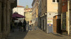 People walking on Via delle Mura on a sunny day in Trieste Stock Footage