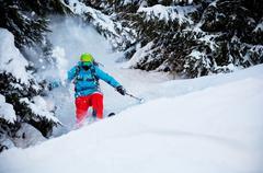 Man freerideer running downhill in forest - stock photo