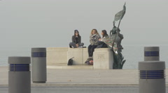 Young women sitting next to bronze statue close to the sea and cars driving Stock Footage