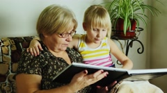 Grandmother with her granddaughter looks an album with family photos - stock footage